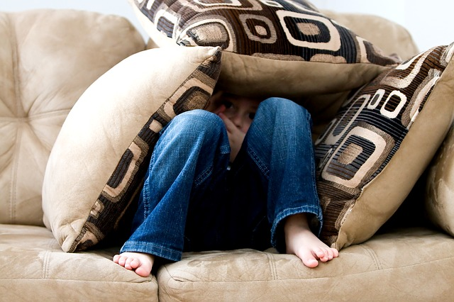 boy hiding under cushions